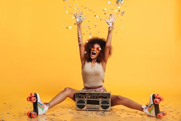 Emotionale afrikanische disko-frau in retro-kleidung und rollschuhen, die konfetti werfen, während sie mit boombox sitzen Kostenlose Fotos