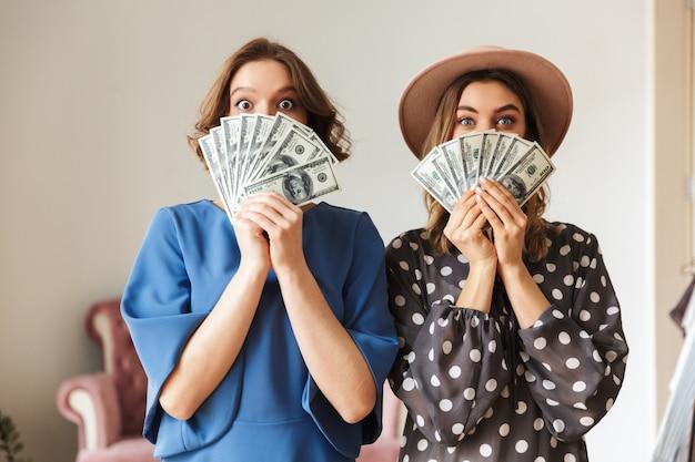 Emotionale junge frauen drinnen, die geld halten. Premium Fotos