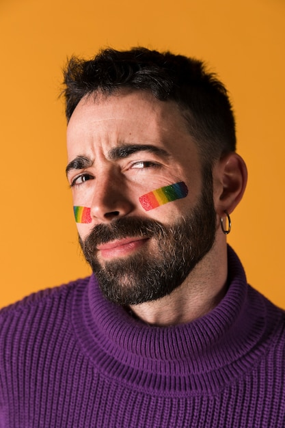 Emotionaler gutaussehender mann mit lgbt-symbol auf gesicht Kostenlose Fotos