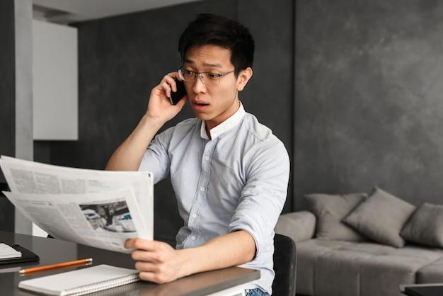 Emotionaler junger asiatischer mann, der per telefon spricht Premium Fotos