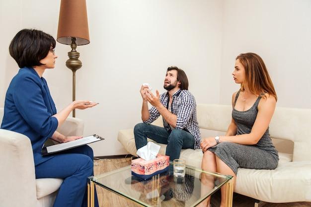 Emotionaler kerl sitzt und weint. er schaut auf und weint. kerl hält trockene serviette in der hand. junge frau sitzt neben ihm und schaut ihn an Premium Fotos