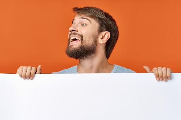 Emotionaler mann, der hinter einem plakat auf einem orangefarbenen modell hervorschaut Premium Fotos
