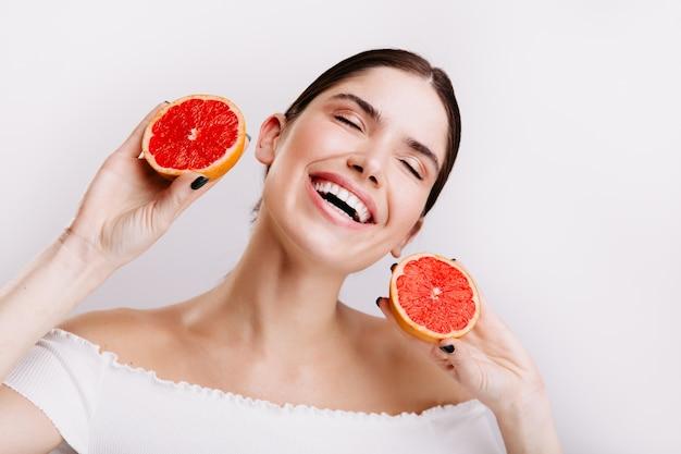 Emotionales mädchen voller energie lacht und posiert mit roten zitrusfrüchten in ihren händen. Kostenlose Fotos