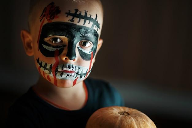 Emotionales porträt eines jungen mit einem furchtsamen zombie auf seinem gesicht und einem kürbis Premium Fotos