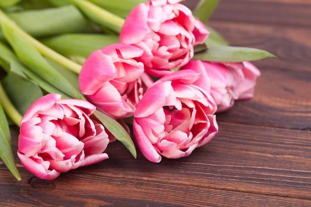 Empfindliche rosa tulpen auf einem braunen hölzernen hintergrund. nahansicht. blumenzusammensetzung. blumenfrühlingshintergrund. valentinstag, ostern, muttertag. Premium Fotos