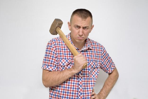 Empörter mann mit einem vorschlaghammer auf einem weiß. arbeit Premium Fotos