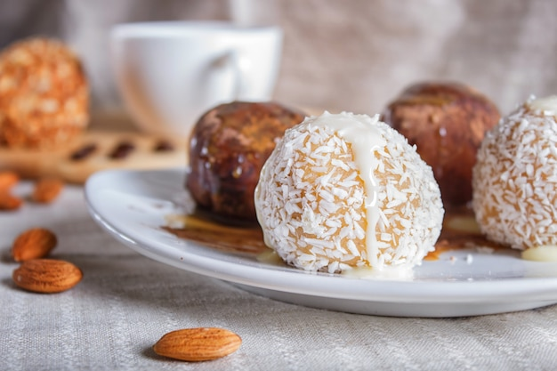 Energiebälle backen mit schokoladenkaramel und -kokosnuss auf weißer platte auf leinenserviette zusammen. Premium Fotos