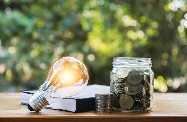 Energiesparende glühlampe mit münzen im glasgefäß für einsparungs-, finanz- und bilanzierungskonzept Premium Fotos