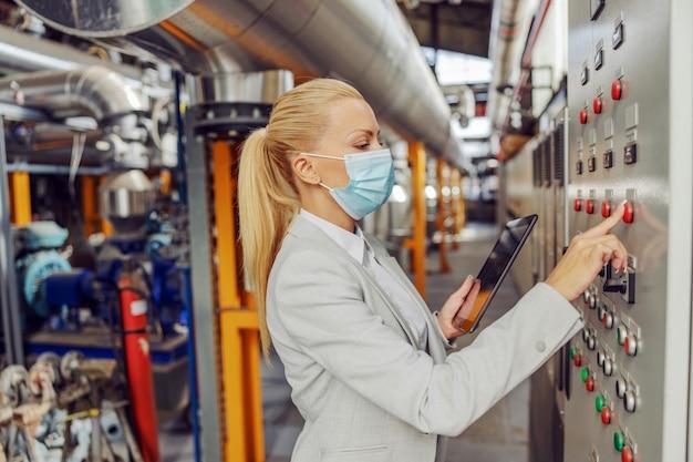 Engagierter weiblicher blonder supervisor mit gesichtsmaske, die in der heizanlage neben dem armaturenbrett steht, einstellungen anpasst und tablette während der koronavirus-pandemie hält. Premium Fotos