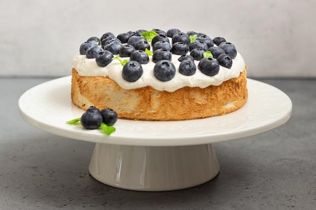Engelsnahrungsmittelkuchen mit schlagsahne und blaubeeren. Premium Fotos