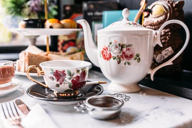 Englische vintage porzellan-rosen-teesätze einschließlich teekanne, teetasse, teller, löffel und teefilter. Premium Fotos