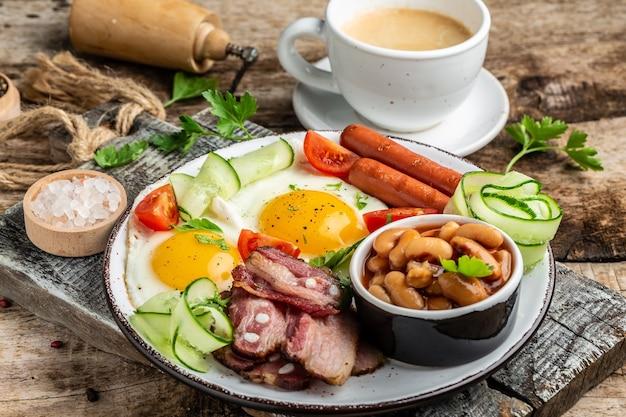 Englisches frühstück mit spiegelei, wurst, speck, bohnen, lebensmittelrezept-tabelle. nahansicht. Premium Fotos