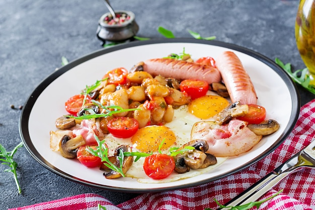 Englisches frühstück - spiegelei, bohnen, tomaten, pilze, speck und wurst. leckeres essen. Premium Fotos