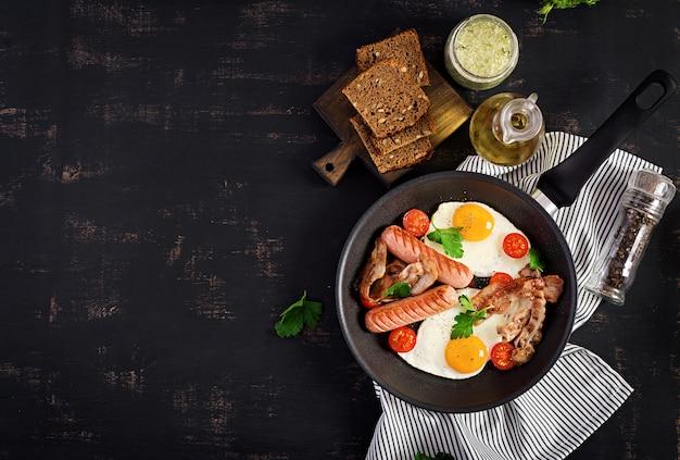 Englisches frühstück - spiegelei, tomaten, wurst und speck. Premium Fotos