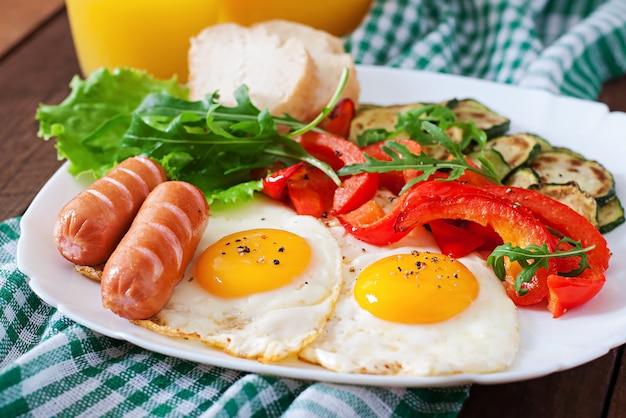 Englisches frühstück - spiegeleier, würstchen, zucchini und paprika Kostenlose Fotos