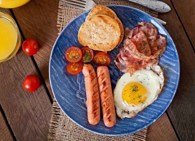 Englisches frühstück - toast, ei, speck und gemüse im rustikalen stil auf holztisch Kostenlose Fotos