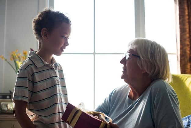 Enkel, der seiner großmutter ein geschenk gibt Premium Fotos