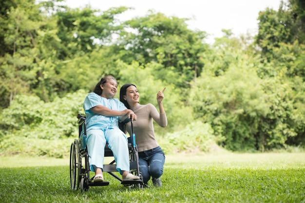 Enkelin, die mit ihrer großmutter sitzt auf rollstuhl, nettes konzept, glückliche familie spricht Kostenlose Fotos