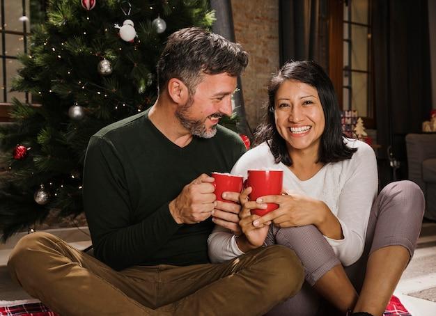 Enoying heiße getränke der glücklichen älteren weihnachtspaare Kostenlose Fotos