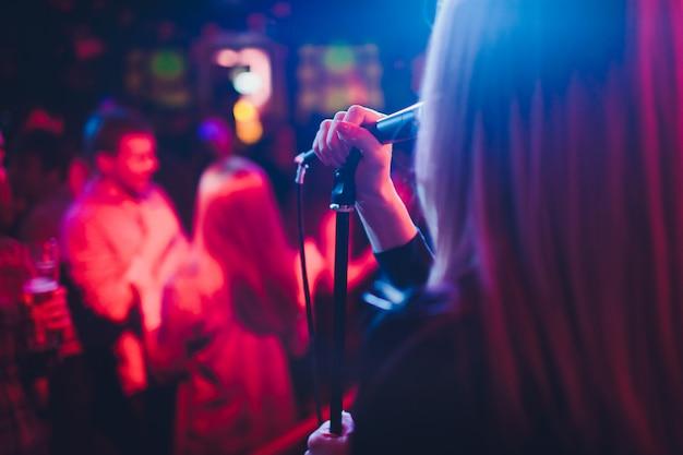 Entertianment bei einer hochzeit. eine sängerin interagiert mit der menge, während ein mann eine akustikgitarre spielt. Premium Fotos
