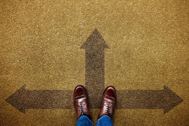 Entscheidung im lebens- oder geschäftskonzept. unentschlossene person, die in vorwärts-, links- und rechtspfeilrichtung steht. draufsicht Premium Fotos