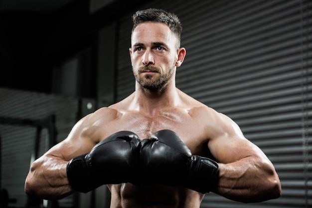 Entschlossener hemdloser mann mit boxhandschuhen an der crossfit turnhalle Premium Fotos