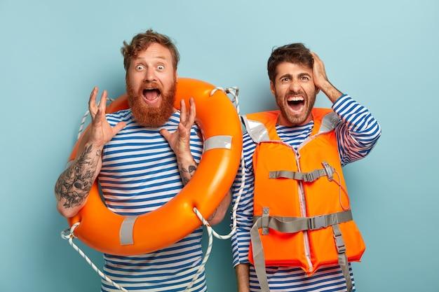 Entsetzte emotionale retter arbeiten am strand als rettungsschwimmer, halten einen rettungsring und tragen eine orangefarbene schutzweste Kostenlose Fotos