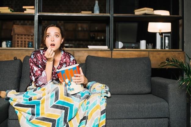 Entsetzte frau, die auf sofa mit aufpassendem fernsehen des popcorns sitzt Kostenlose Fotos