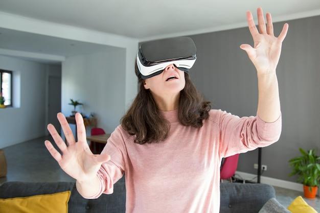 Entsetzte junge frau, die welt im kopfhörer der virtuellen realität lernt Kostenlose Fotos