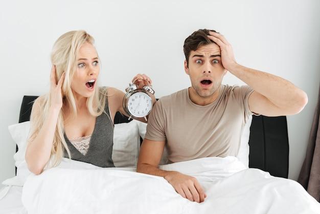 Entsetzte junge paare, die im bett mit geöffnetem mund sitzen und wecker halten Kostenlose Fotos
