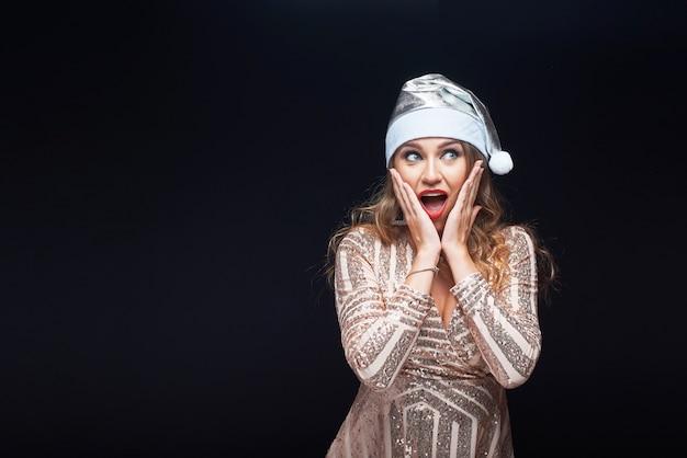 Entsetzte schöne frau im kleid und in weihnachtsmann-hut getrennt auf schwarzem. Premium Fotos