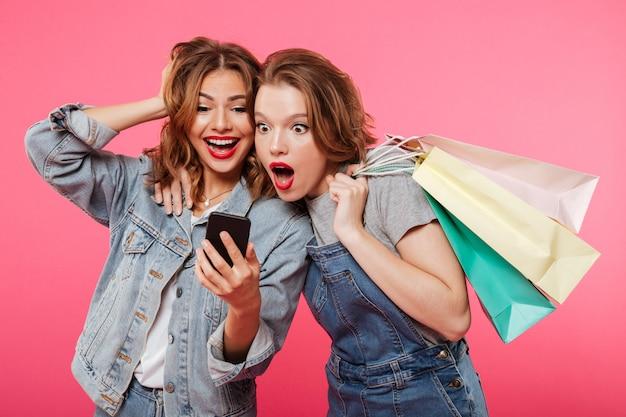 Entsetzte zwei freundinnen, die einkaufstaschen unter verwendung des handys halten. Kostenlose Fotos