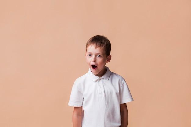 Entsetzter junge mit dem offenen mund, der nahe beige hintergrund steht Kostenlose Fotos