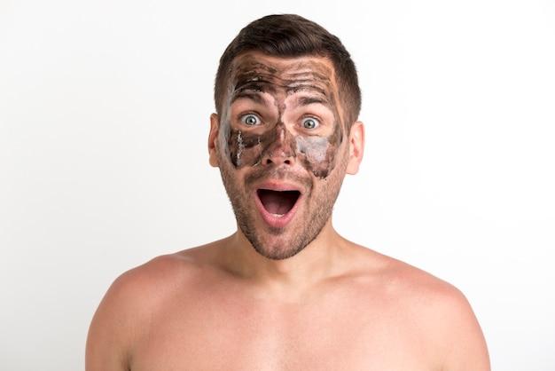 Entsetzter junger mann mit schwarzer maske auf gesicht über weißer wand Kostenlose Fotos