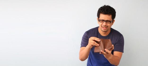 Entsetzter, überraschter sprachloser mann, der eine leere geldbörse auf weiß hält. Premium Fotos