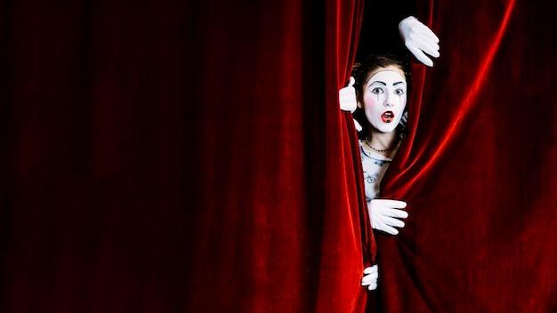 Entsetzter weiblicher pantomimekünstler, der vom roten vorhang späht Kostenlose Fotos