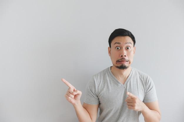 Entsetztes gesicht des mannes im grauen t-shirt mit handpunkt auf leerem raum. Premium Fotos