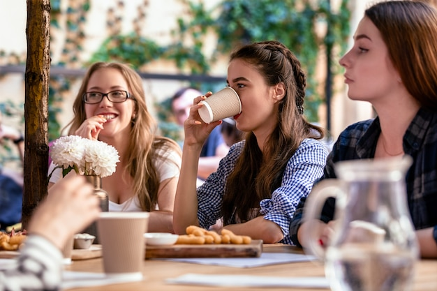 Entspannen sie mit den besten freunden auf der terrasse eines örtlichen cafés an heißen, sonnigen tagen Kostenlose Fotos