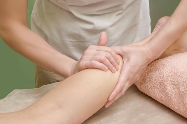 Entspannende professionelle massage am weiblichen bein (beinwade) im salon. Premium Fotos