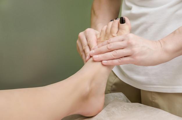 Entspannende professionelle massage am weiblichen fuß im salon. Premium Fotos