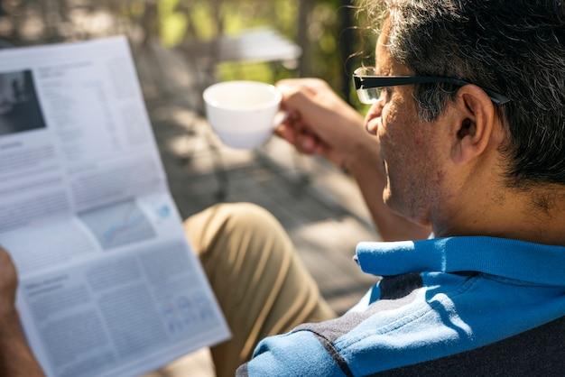 Entspannender mann beim lesen einer zeitung und beim kaffeetrinken Kostenlose Fotos