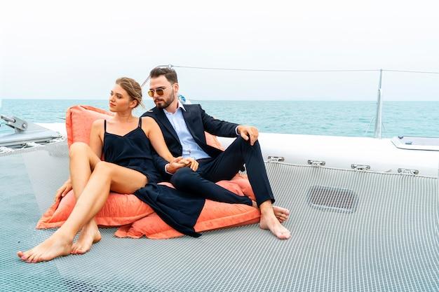 Entspannender paarluxusreisender im netten kleid und in der reihe sitzen auf bohnentasche im teil der kreuzfahrtyacht. Premium Fotos