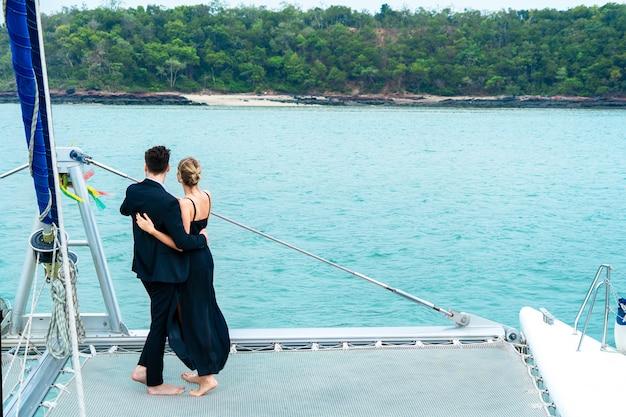 Entspannender paarluxusreisender in nettem kleid und anzug stehen an der front in der kreuzfahrtyacht. Premium Fotos