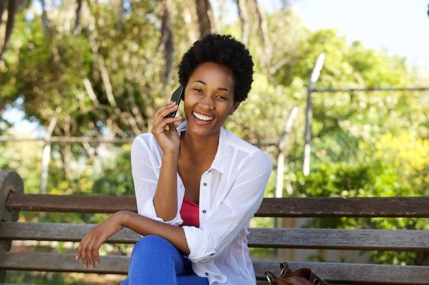 Entspannte afrikanische frau, die auf einer parkbank sitzt und handy verwendet Premium Fotos