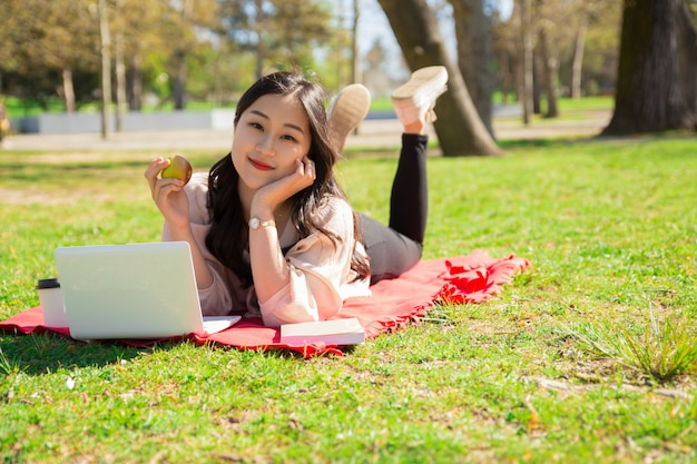 Entspannte asiatin, die apfel hält und laptop auf rasen verwendet Kostenlose Fotos