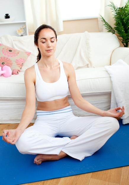 Entspannte frau, die das yoga sitzt in ihrem wohnzimmer tut Premium Fotos