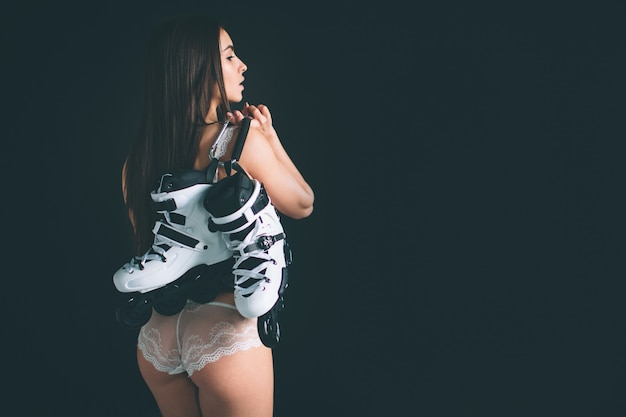 Entspannte freudige passform frau hält inline-rollschuhe. junge frau mit langen schwarzen haaren steht isoliert auf schwarzem hintergrund. das mädchen hat eine sportfigur, sie trägt weiße unterwäsche. Premium Fotos