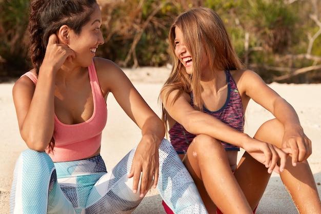 Entspannte, fröhliche, junge frauen gemischter rassen sehen sich freudig an, ruhen sich gut an der küste oder an der küste aus, gekleidet in sportkleidung Kostenlose Fotos