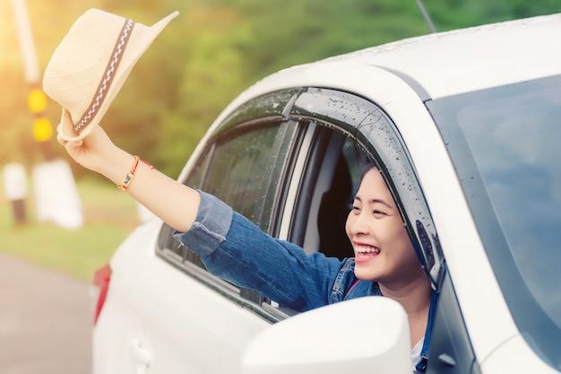 Entspannte glückliche frau auf den sommer roadtrip reiseferien, die heraus autofenster der naturansicht betrachten Premium Fotos