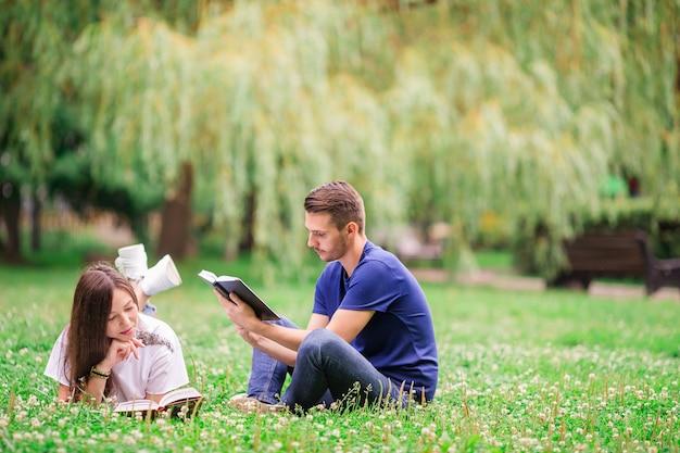 Entspannte junge paarlesebücher beim lügen auf gras Premium Fotos